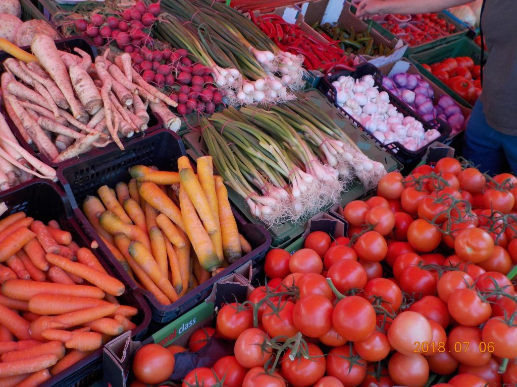 This picture shows a vegetable stand at an open-air market: featured are tomatoes, carrots, green onions, radishes, horseradish, garlic, and peppers.