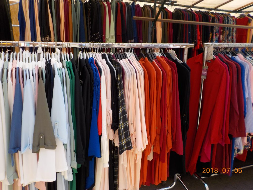 This image shows clothing hanging at a market. Pictured are numerous blouses and tunics on racks.