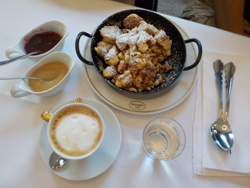 "This picture shows the Austrian dessert ""Kaiserschmarrn"" with 2 sauces on the side: apple sauce and plum sauce. On the table there is also a cup of coffee."