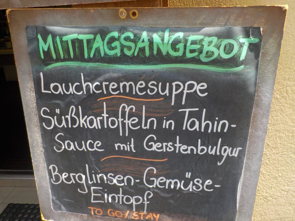 "This picture shows the specials of the day (""Mittagsangebot"") in a vegan cafe."