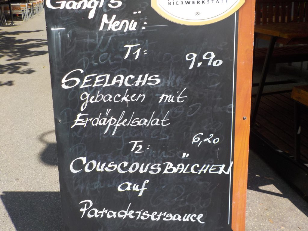 This picture shows a restaurant sign with today's specials (Menü): the two options are Lachs mit Salat oder Couscousbällchen mit Suppe.