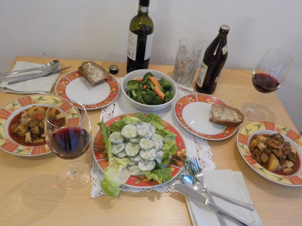 Table spread of salad, bread, and a main dish of meat and potatoes
