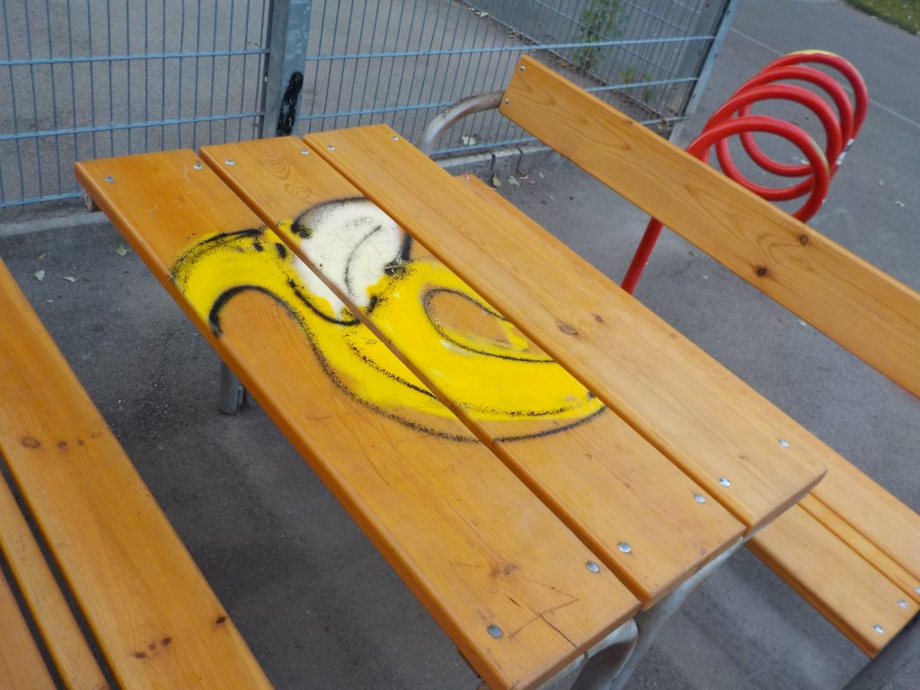 This photo shows a spray-painted banana on a wooden table in a park in Vienna.