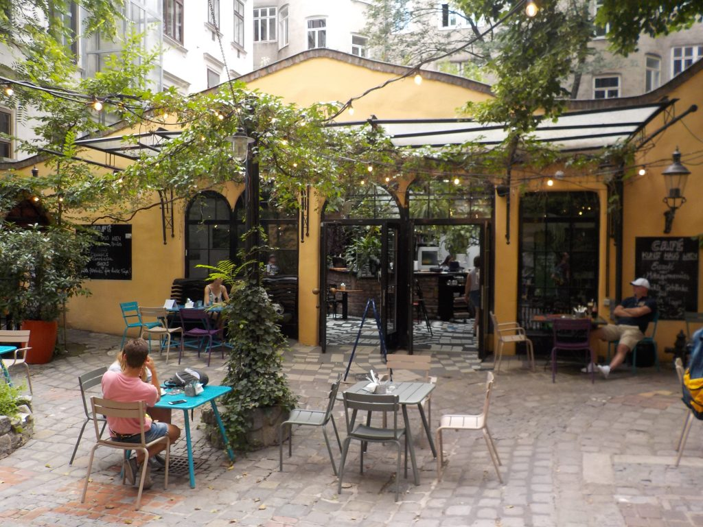 This picture shows an inviting outdoor cafe surrounded by vines and greenery.
