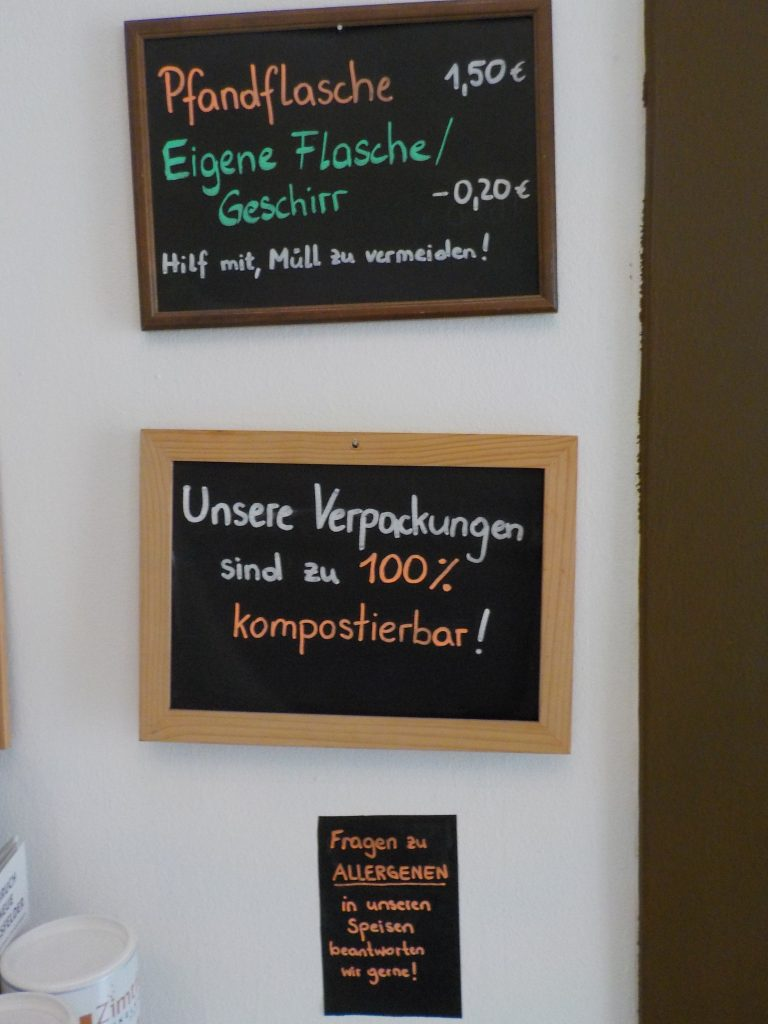This picture shows three signs in a vegan cafe that communicate their efforts to be sustainable: there is a deposit on all bottles and a discount for any customer who brings their own packaging; the café's packaging is compostable, and the employees gladly answer questions about allergens.