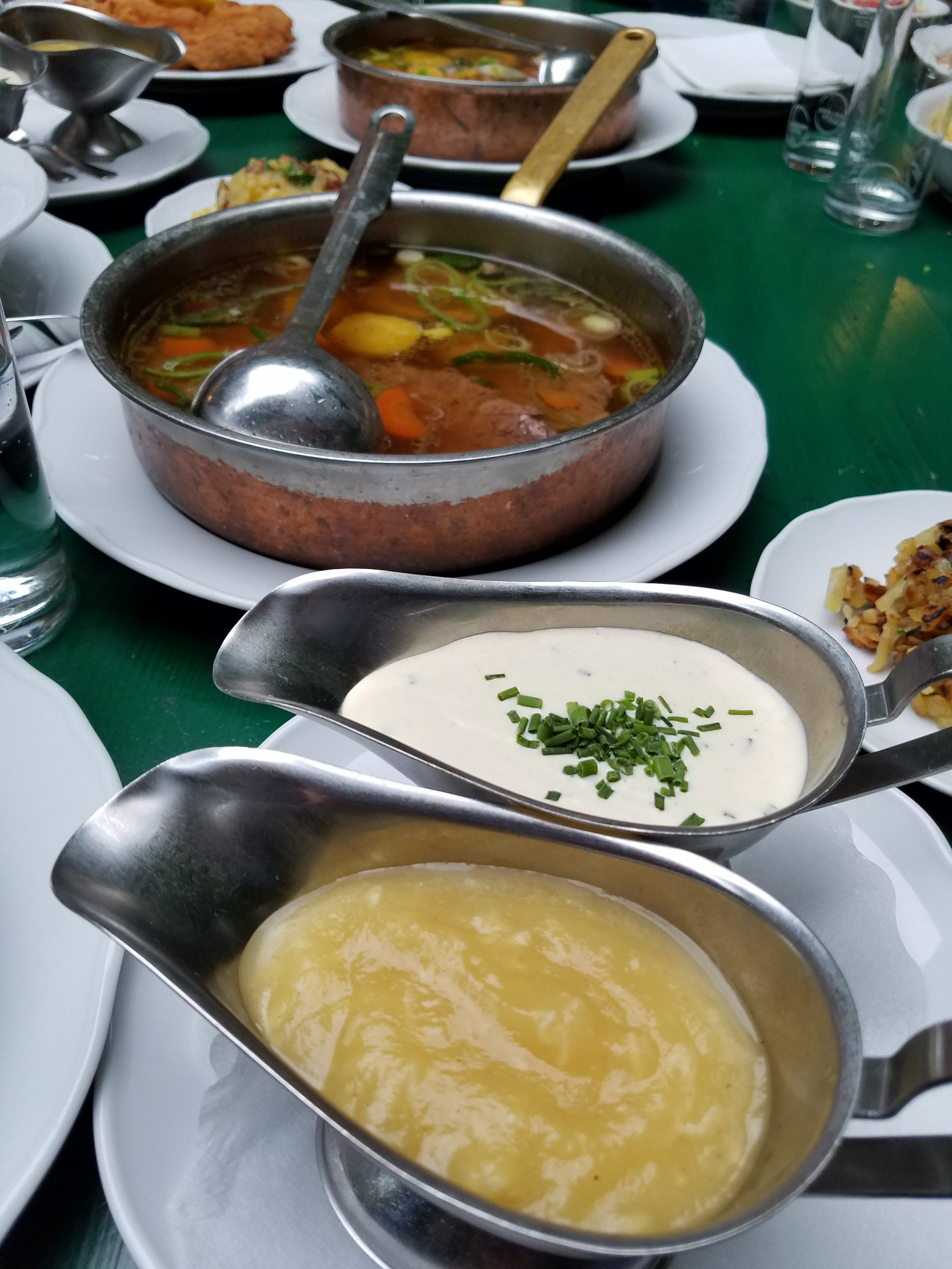 This images shows an Austrian culinary specialty. A pot of vegetable broth with a spoon in it sits on a table next to two gravy boats filled with sauces. Beef or veal is typically cooked in the broth and then served in the pot with sauces on the side.