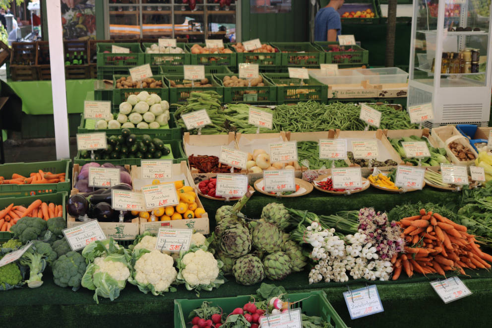 Picture of vegetable stand with cauliflower, broccoli, carrots, eggplant, artichokes, radishes, beans, and other vegetables.
