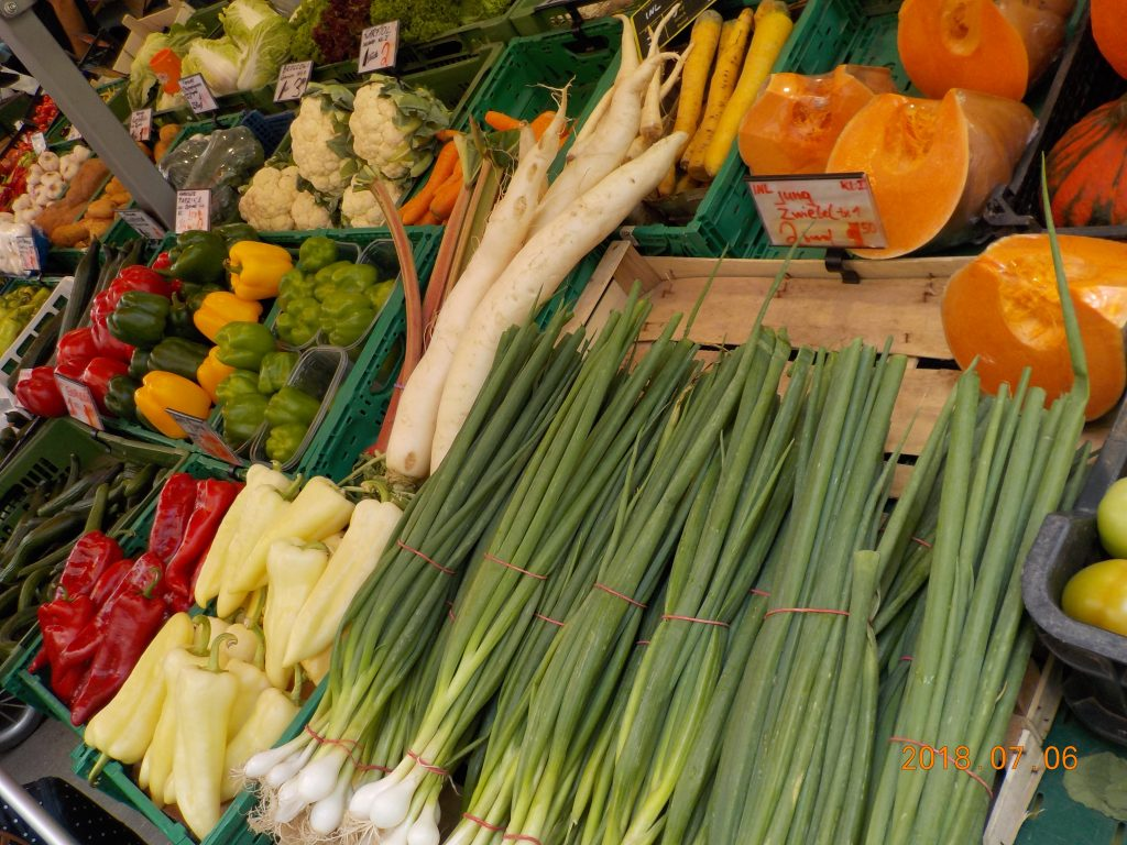 This picture shows a market stand with green onions, radishes, assorted peppers, cauliflower, and other vegetables.