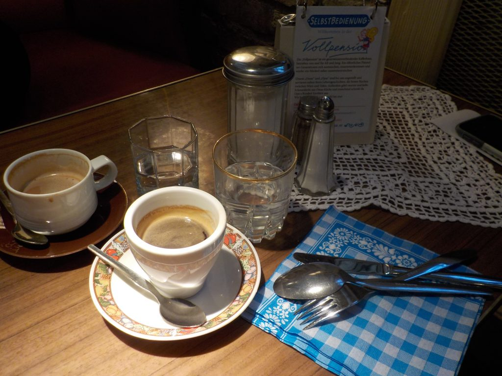 A Sunday morning in a café. The image shows a coffee cup and flatware on a table.