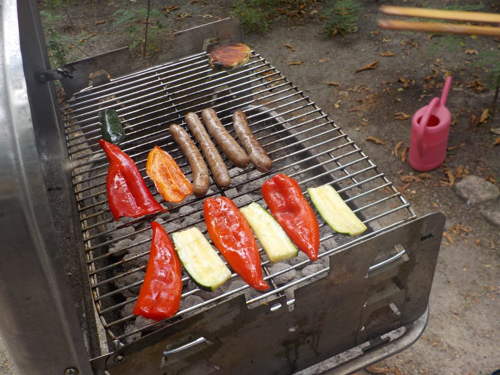 Sausages and vegetables cooking on an outdoor grill