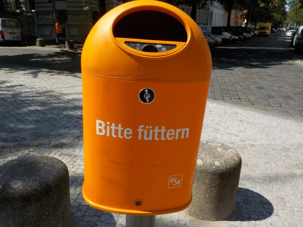 """This picture shows an organ trash can in the city bearing the words """"bitte füttern"""" on it."""