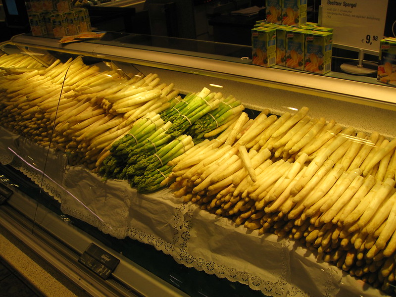 Decorative photo of white & green asparagus on display in a market.