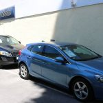 blue and black cars in front of car dealership