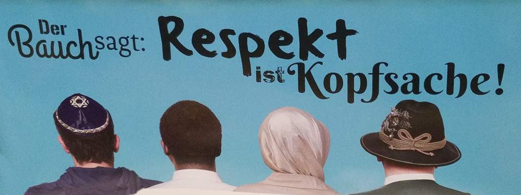 """Subway ad showing four heads, one uncovered, one in a Jewish kippah, one in a Muslim headscarf or hijab, and one in a traditional Tirolean hat, reading """"Der Bauch sagt, Respekt ist Kopfsache."""""""