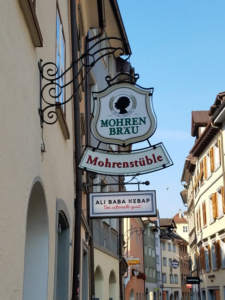 """The background shows a picturesque Austrian town street while the foreground features a sign reading """"Mohrenbräu"""" and """"Mohrenstüble"""" and containing a racist caricature."""
